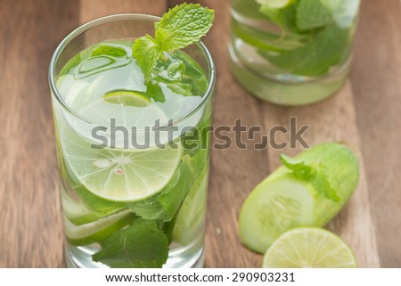 Detox water, lime with cucumbers and mint in glass. Downward vie - stock photo