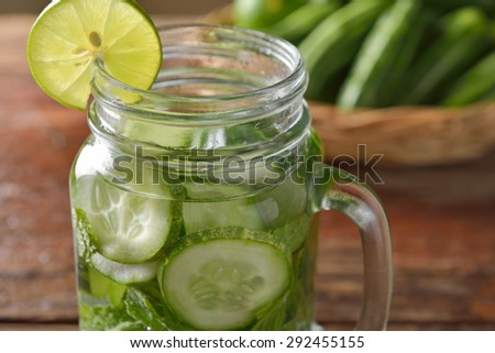 Detox water with lime and cucumbers in a mason jar against a rustic wood background - stock photo