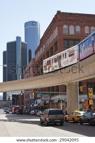 DETROIT - April 11, 2009 - With the headquarters of the financially ailing General Motors in the background, the People Mover crosses a street in Detroit's Greektown. GM is facing possible bankruptcy. - stock photo