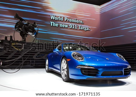 DETROIT - JANUARY 13 :A video camera captures video footage of the new Porsche 911 Targa on display at the North American International Auto Show media preview  January 13, 2014 in Detroit, Michigan. - stock photo
