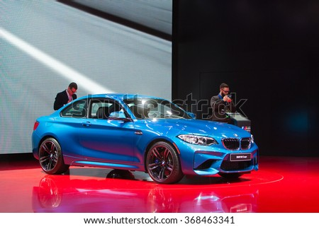 DETROIT - JANUARY 12: Members of the media look at the new BMW M2 Coupe on display at the North American International Auto Show media preview January 12, 2016 in Detroit, Michigan. - stock photo