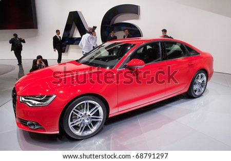 DETROIT - JANUARY 10: Reporters inspect the new 2011 Audi A6 at the 2011 North American International Auto Show Press Preview on January 10, 2011 in Detroit, Michigan.