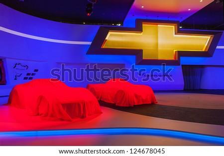 DETROIT - JANUARY 14 : Vintage Corvettes sit under covers at the 2014 Chevrolet Corvette unveiling January 14, 2013 in Detroit, Michigan. - stock photo