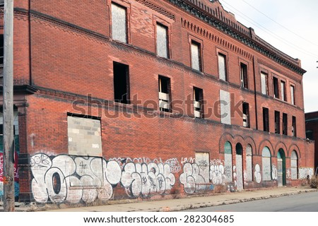 DETROIT, MI-MAY, 2015:  Abandoned apartment building with graffiti on the side of the building near downtown Detroit.   - stock photo