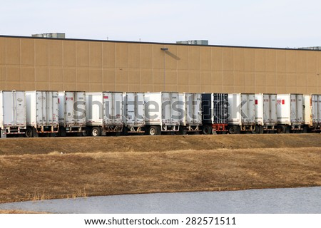 DETROIT, MI-MAY, 2015:  Rear view of trucks waiting to be unloaded at a warehouse or industrial site.   - stock photo