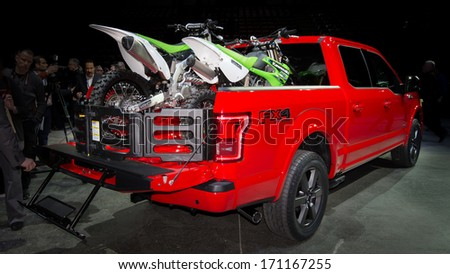 DETROIT, MI/USA - JANUARY 13: A 2014 Ford F150 FX4 truck carrying two Kawasaki KX-85 dirt bikes at the North American International Auto Show (NAIAS) on January 13, 2014, in Detroit, Michigan. - stock photo
