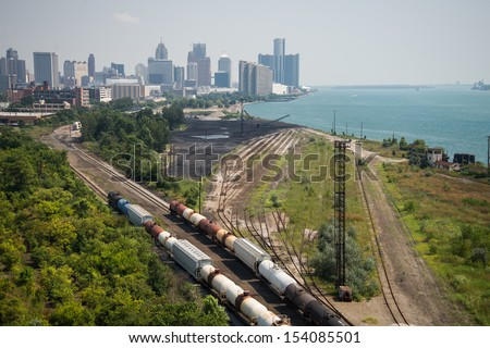 Detroit Michigan Railroad - The railroad and shipping docks along the Detroit River with downtown Detroit, Michigan in the background on a hazy summer day.  - stock photo