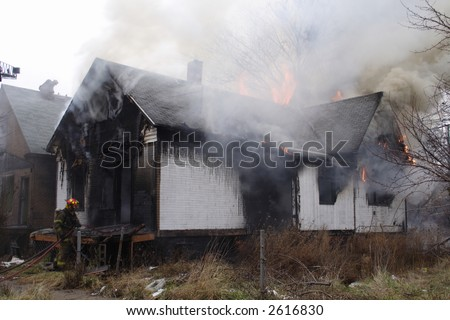 Detroit neighborhood house in flames and billowing smoke - stock photo