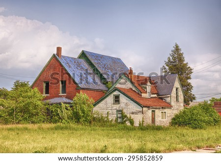 DETROIT, USA - JUNE 9, 2015: An abandoned house with broken windows located next to an empty lot full of weeds  symbolizes urban decay in post-industrial Detroit. - stock photo