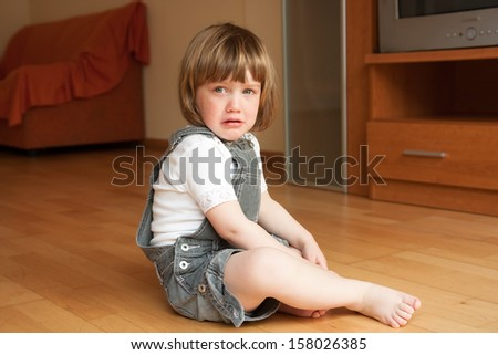 detuned little girl on the floor - stock photo