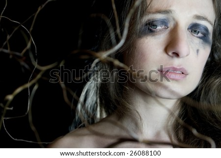 Devastated young woman on black background. Branch next to her face. - stock photo