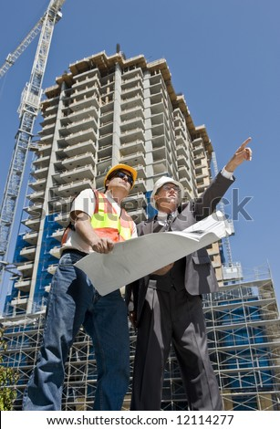 Developer and construction foreman looking over blueprints of a hirise construction project - stock photo