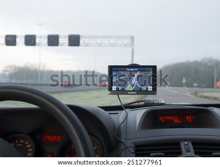 DEVENTER, NETHERLANDS - FEBRUARY 7, 2015: Garmin gps navigation device in a car. Garmin is one of the largest manufacturers of GPS devices. - stock photo