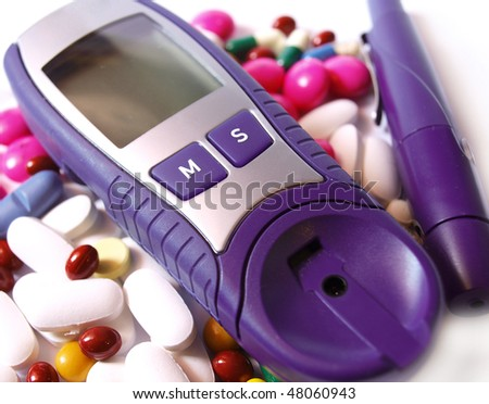 Device for measuring blood sugar level and pills - stock photo