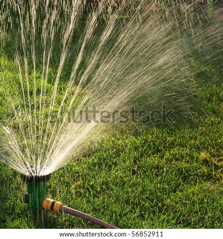 Device of irrigation garden. Irrigation system -  technique of watering in the garden. Lawn sprinkler spraying water over green grass. - stock photo
