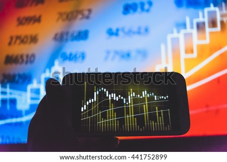 Device on hand to check stocks and market data. Market graph with arrows tending.Digital Marketing Graph Statistics Analysis Finance Market Concept. Marketing Analysis Accounting from digital chart.