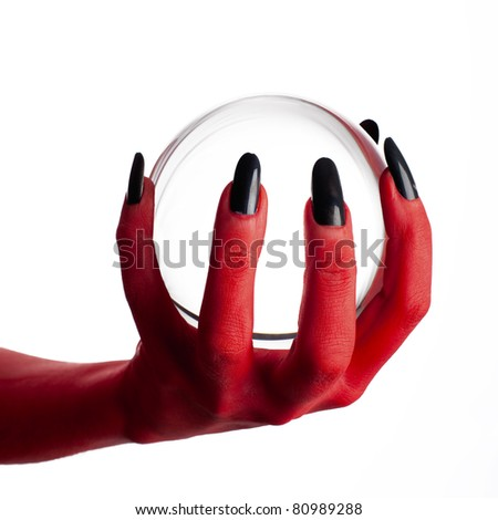 Devil's hand holding crystal ball, white background. - stock photo