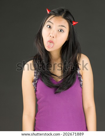 Devil side of a young Asian woman sticking out her tongue - stock photo