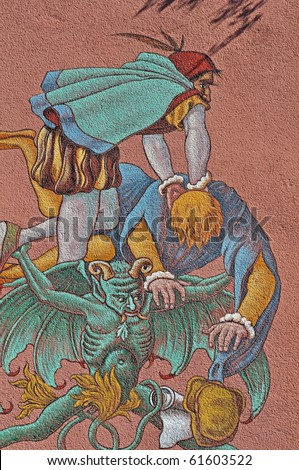 Devil takes Doktor Faust to hell - scene on a wall in Staufen,Germany where the real Dr. Faust has lived till he died in this house - stock photo