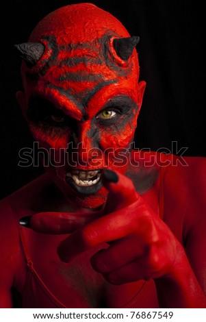 Devil woman pointing her finger. Low key lighting. - stock photo