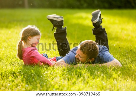 Devoted father and daughter enjoying eachothers company, bonding, talking, having fun in nature on a bright, sunny day. Parenthood, lifestyle, parenting, childhood and family life concept.  - stock photo