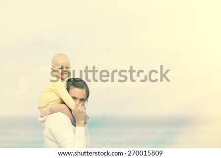 Devoted mother and adorable child cuddling, spending quality time on the beach. - stock photo