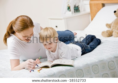 Devoted mother coloring in coloring book with son on bed in bedroom