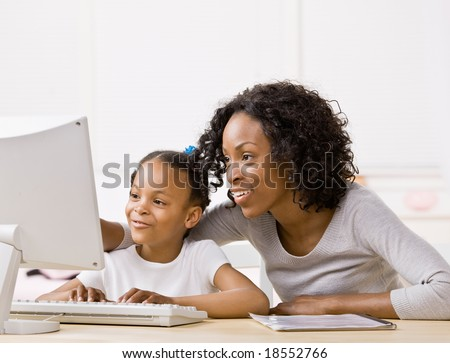 Devoted mother helping girl do homework on computer - stock photo