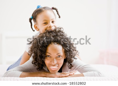 Devoted mother lays on bed with playful daughter - stock photo