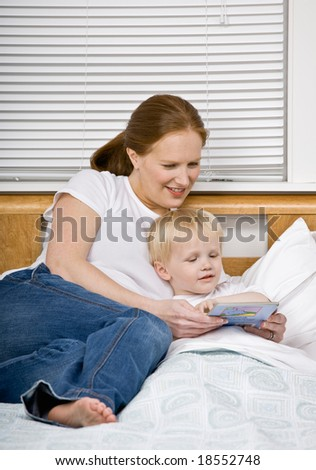 Devoted mother reading son a bedtime story in bed