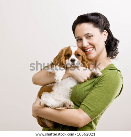 Devoted woman holding and comforting pet dog - stock photo