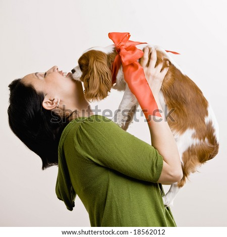 Devoted woman kissing pet dog with bow - stock photo