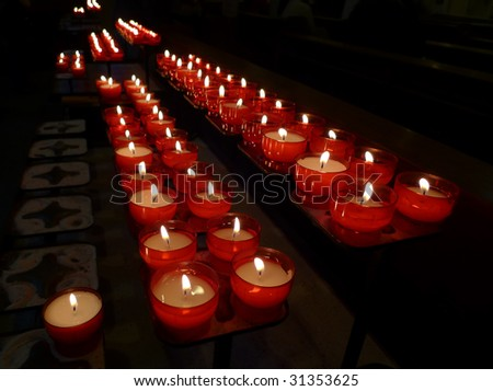 Devotional candles flaming in the dark of a church - stock photo
