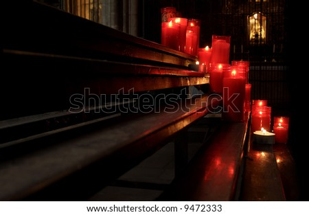 Devotional candles flaming in the dark of an spanish church - stock photo