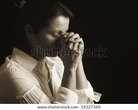 Devout woman with eyes closed in prayer - stock photo