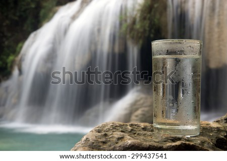 Dewy glass of water on a background of a waterfall. Glass full of fresh water at the source in nature. Mineral water in a glass with a waterfall in the forest. Glass of water with blurred waterfall. - stock photo