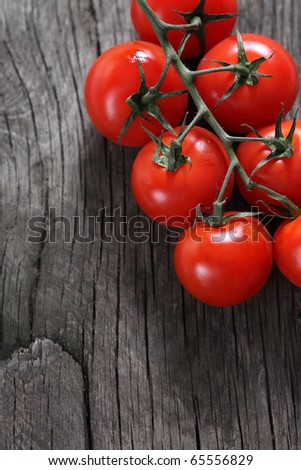 Dewy red tomatoes on the rustic wooden board - stock photo