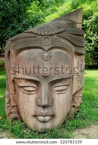 Deyang, China - July 8, 2007:  A giant Buddha head sits on a lawn at the Stone Carvings Park