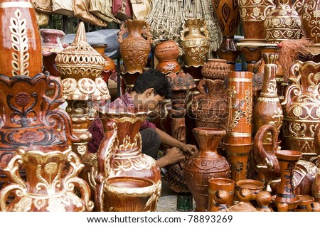DHAKA, BANGLADESH – SEPTEMBER 21: Unidentified young man paints clay-made pottery in a roadside shop on September 21, 2010 in Dhaka, Bangladesh. Shops like this sell handcrafts to tourists and locals. - stock photo