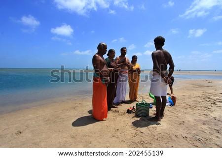 DHANUSHKODI, INDIA - OCT 06: Unidentified Hindu family do rituals at the sacred confluence on October 06, 2013 in Dhanushkodi, Tamil Nadu, India. Dhanushkodi is a Hindu pilgrimage site in India. - stock photo