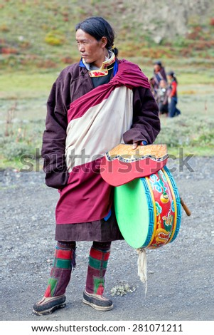 DHO TARAP, DOLPO, NEPAL - SEPTEMBER 11: Man in national clothes with Tibetan drum waiting for Puja ceremony during Full Moon festival on September 11, 2011 in Dho Tarap village, Nepal - stock photo