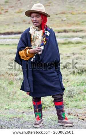 DHO TARAP, DOLPO, NEPAL - SEPTEMBER 11: Tibetan nomad in traditional clothes offering flowers during Dho Tarap Full Moon Festival on September 11, 2011 in Dho Tarap village, Nepal. - stock photo