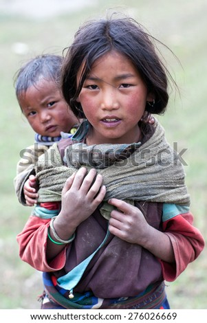 DHO TARAP, NEPAL - SEPTEMBER 10: Nepalese girl with her baby brother walkig on the road on September 10, 2011 in Dho Tarap village, Upper Dolpo, Nepal