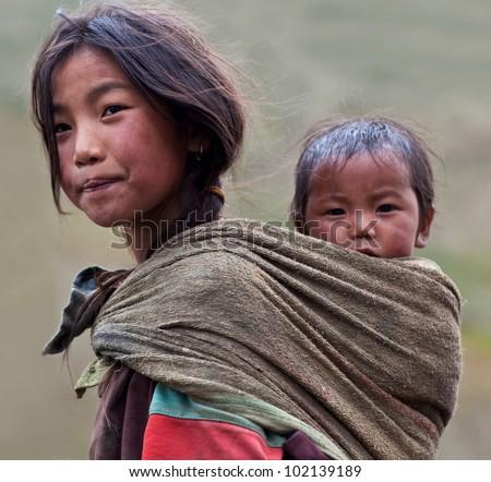 DHO TARAP - SEPTEMBER 10: Tibetan girl Ningma Dolkar, 9, from the village of refugees poses for the photo during the Dho Tarap Full Moon Festival on September 10, 2011 in Dho Tarap, Upper Dolpo, Nepal - stock photo