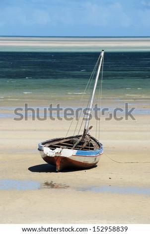 Dhow on a sand bank, Mozambique. Portrait. - stock photo