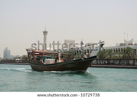 Dhow Traveling on Historic Dubai Creek - stock photo