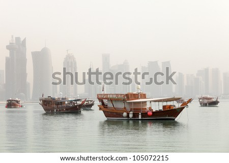 Dhows in Doha Bay, Qatar, June 2012, with the Arab capital's 21st Century skyline still under construction in the background, partly obscured by mist from the hot Gulf waters. Stitched panorama. - stock photo