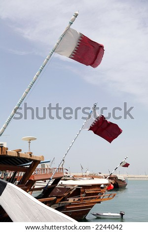 Dhows tied up in the Dhow Harbour, Qatar, with the national flag flying from their stern flagstaffs. - stock photo