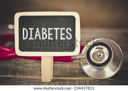 Diabetes and stethoscope. Medecine concept. Blackboard with word diabetes and stethoscope - stock photo