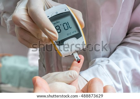 Diabetes concept. Doctor is monitoring blood glucose level of diabetic patient.